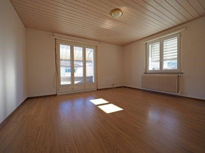 sonniges Wohnzimmer mit Zugang auf den Balkon
