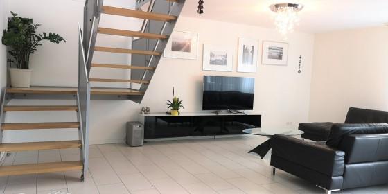 Wohnbereich mit Treppenaufgang zur nächsten Etage