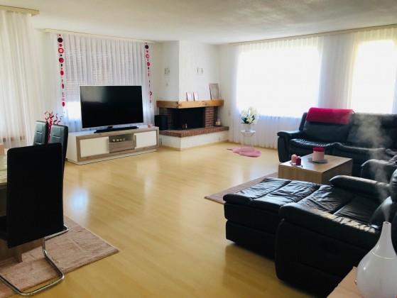 Wohnzimmer mit Cheminée und Balkonzugang