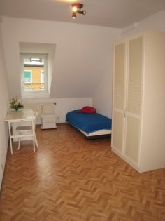 Dachzimmer mit Pult, Bett und Schrank